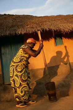 Africa | Congolese Woman  pounds manioc (cassava) leaves in preparation of a cooking a meal for the family.