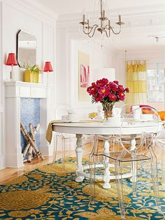 Transparent chairs let the gorgeous floral pattern on the rug shine through.