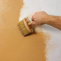 Lehmfarbe wird mit einem Quastenpinsel auf die Wand aufgetragen