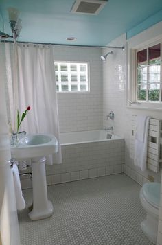 combination of honeycomb tile and subway tile with pedestal sink and color pop on ceiling