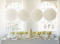 large balloons and simple flowers give this sweets table wow factor.