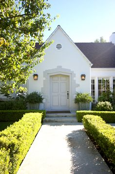 Painted white home with off-white door and frame (and a great green path to the door!)