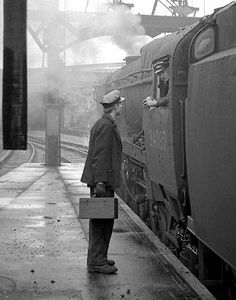 Fireman Ronald Whittaker chats to the driver of an eastbound express at Bournemouth Central, England on 23rd May 1965. Negative scan.