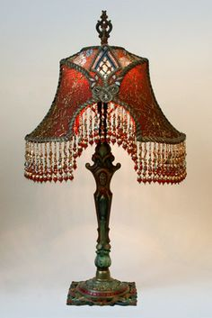 Ornate painted 1920s metal lamp holds a gold and red Napoleon shade covered in gold metallic lace, embroidered net and Victorian-era passementerie appliqués. Hand beaded fringe in matching tones.