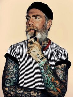 Tattooed old and wise man in a sailor man outfit