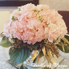Blush pink hydrangea with pink carnations and wax flowers. The fluff petals of carnations blend easily with hydrangea so will cut down your cost on centrepiece. Ask your florist.