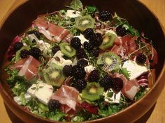 Salad with blackberries, prosciutto, brie cheese, kiwi and fresh thyme