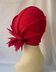 Unique and exclusive design for this 20s style cloché hat made in 100% wool feltl hand modeling. This hat is in red comes with a flower on the