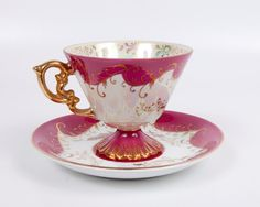 Footed teacup and saucer in hot pink w. gold lustre.