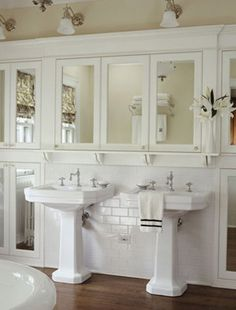 kids bathroom - pedestal sinks and lots of deep mirrored medicine cabinets