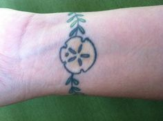Wrist tat of sand dollar w seaweed that wraps around. Delicate & has personal meaning. It is one of my favorites for sure! Done by my amazingly talented sister too!! Stop by Good Fortune Tattoos in Savannah!