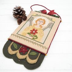 Pinner said:  A beautiful Christmas angel cross stitched in shades of gold and silver embroidery floss, holds a single cranberry colored flower in her