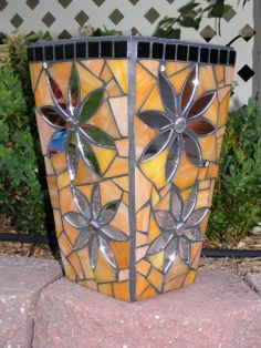 Orange glass, mirror, ceramic mosaic tiles, on terracotta pot.