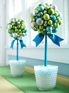 remove the caps from glass or plastic ball ornaments and attach the ornaments to a foam ball with hot glue. Insert a dowel into the foam ball. Tightly wrap the dowel in ribbon, stopping before you reach the bottom. Fill a hobnail vase or other container half-full with modeling clay; insert dowel. Top clay with marbles.