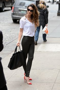 supersleek in a black leather Citizens of Humanity jeans, a crisp white Lily Aldridge for Velvet tee, and red cap-toe pumps in NYC. She completed her tricolored ensemble with a black tote bag, cat-eye sunglasses, and a shiny rhinestone necklace.
