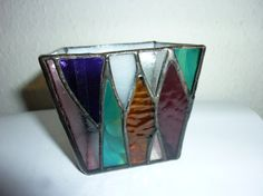 Stained glass candle holder. Front desigh image is forest(geometry) Glass colour blue,purple,reddish brown etc. Side and back glass are smoky white glass. Size aprox 8 cm width) x 8 cm(height) x 6 cm(bottom) This box has a black patuna finish.