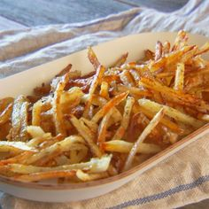 Oven-baked fries are tossed with olive oil, fresh grated cheese, and a medley of dried Italian herbs for a twist on an old favorite.