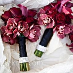 Wedding bouquet of dark burgundy calla lilies with white roses, hand tied with…