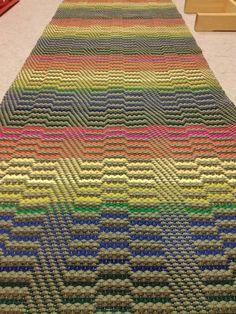 Onnenpolku-matto Kaksi vihreää kudetta läpi maton ja yhtä vaihdettu erilaisilla kirkkailla sävyillä.