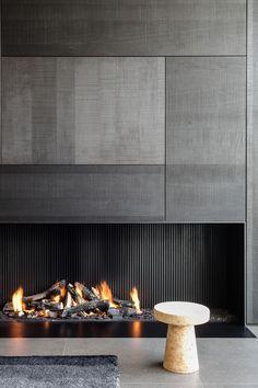 Idea camino aperto a legna stile moderno con la parete rivestita con lastre di ceramica grigia