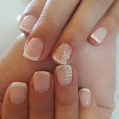 Nude nails with traditional white French tip and white floral design on ring fingernail