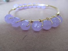 Light periwinkle colored stones on gold bangle jewelry! Stack this bracelet with dark purple, white, or clear for a girly look!