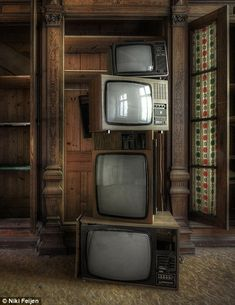 A stack of old television sets of different sides and front different eras...