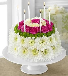 """The FTD® Wonderful Wishes™ Floral Cake is set to celebrate their birthday with sweet sentiments blooming with chrysanthemums and carnations. Perfectly arranged in the shape and styling of a colorful birthday cake are white chrysanthemums, green button poms, pale yellow carnations and magenta mini carnations. Presented on a white cake plate, this memorable flower arrangment will add to the festivities of their special day.  Approximately 9""""H x 10""""W with plate."""