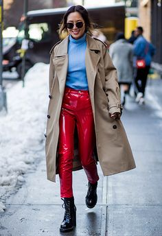 Aimee Song attending New York Fashion Week wearing red PVC trousers, a blue ribbed knit, an olive green trench coat and a pair of heeled combat boots | ASOS Fashion & Beauty Feed