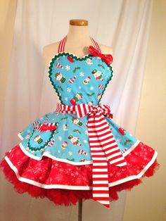 Hello Kitty is ready for Christmas! The gifts are wrapped and the stockings are filled, Lets party! This fun and flirty apron features an adorable combination of the blue HK Christmas fabric, red and white stripe candy cane fabric and red and white snowflake fabric.  The bodice has a sweetheart neckline that features the Hello Kitty fabric, topped off with a big bow in the red and white snowflake fabric. The bodice is fully lined and edged in white bias. The neck strap is adjustable with a…