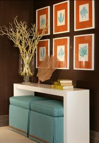 Good idea for small desk.  Storage ottomans double as seating and storage for supplies/files. love the framed pictures