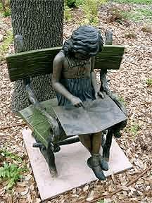 Young girl reading on a bench, installed in memory of Jana Joseph, near the Memorial Garden.