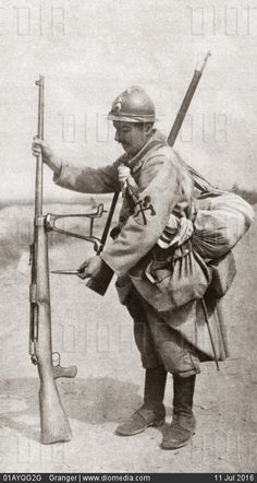 WWI; German soldier holding an anti-tank rifle and the bullet it shoots. -diomedia.com