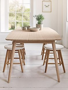 Scandinavian style dining room furniture from Cox and Cox featuring a dining room table, dining room chairs, low stools, bar stools and a useful console table.