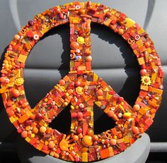 12 peace sign mosaic covered with glass tiles, beads, millefiori, jewelry pieces, buttons in different shades of orange. Ready to hang. For inside