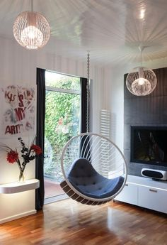 white powder coated steel wire hanging bubble chair with grey cushion below two moon shades pendant lights all items designed by ben rousseau