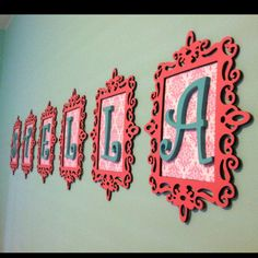 $1 wooden frames spray-painted pink, girly scrapbook paper, and painted wooden letters from the craft store. So pretty for the girls' room!