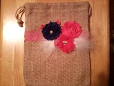 Burlap dollar dance bag embellished with navy blue and shades of  pink shabby flowers and a feather.