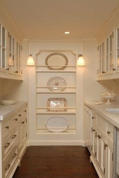 Butler's pantry!  Love that they took dead space at the end and borrowed room in between the studs to create visual interest with the platter storage