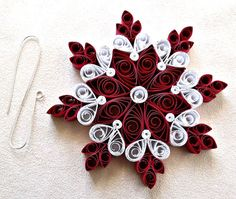"This hand quilled snowflake is made from paper quilling strips which are 3/8"" (1 cm) wide in shades of red and white. It is accented with silver"