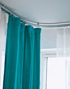 Blue and white curtains on a KVARTAL track control the light in the bedroom.