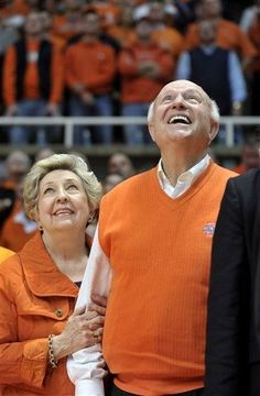 Such greatness    Former Illinois coach Lou Henson, with his wife, Mary Henson, watches a video presentation showcasing his history with Illinois men's basketball, before his coaching banner was displayed at halftime of an NCAA college basketball game between Ohio State and Illinois in Champaign, Ill., on Tuesday, Jan. 10, 2012. (AP Photo/Heather Coit)