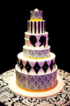 The ornate wedding cake was decorated in black and white damask   with silhouettes, sugar pearls and pops of orange ribbon.