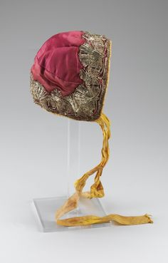 Child's cap, Norway, second half 18th century. Red silk taffeta, metall lace decoration, yellow silk ribbon binding.