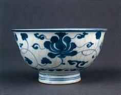 Porcelain bowl with rounded sides, everted rim and high, slightly flaring foot. Decorated in underglaze cobalt blue. Chrysanthemum and lotus scrolls on the outside, and a single chrysanthemum spray in a double ring inside. Mark on base. (Ming dynasty)