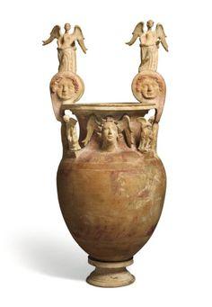 Grand cratère dont la panse est peinte de deux scènes historiées représentant des chevaux. Le col est orné d'une tête de génie ailé coiffé d'une couronne végétale, et des mascarons représentant des Gorgones ornent le haut des anses. L'épaule est ornée de deux statuettes d'Éros nu, ailé, tenant une torche renversée, et les anses sont surmontées de deux statuettes de Victoire ailée (Niké) - Terre cuite et traces de polychromie - Grande Grèce, Canosa, IVe-IIIe siècle avant notre ère. H: 81,5 cm