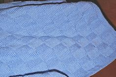 This garter stitch check baby blanket knitting pattern is suitable for all knitters including beginners.