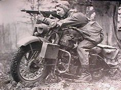 A US Army private on a Harley Davidson 'Liberator' shooting with his Thompson gun, uknown location, unknown date.