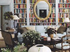 Bookshelves;   A wall of books with a gold gilt oval mirror almost as a piece of artwork being displayed, reflects light.    The Gloss Autumn 2011