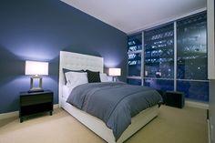 peinture bleu dense dans la chambre à coucher moderne, lampes de chevet métalliques et moquette en beige clair